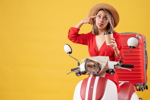 Vooraanzicht jonge dame in rode jurk die tong uitsteekt met koffiekopje in de buurt van bromfiets