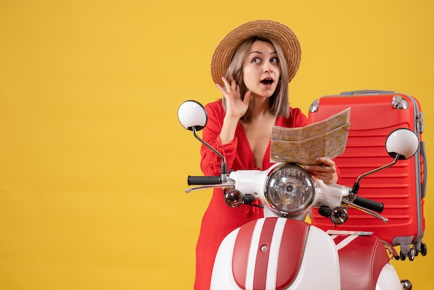 Vooraanzicht jonge dame in rode jurk met kaart luisterend naar iets in de buurt van bromfiets