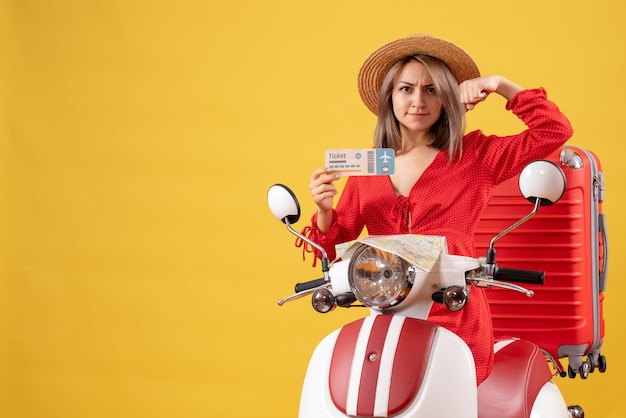 Vooraanzicht jonge dame in rode jurk met kaartje met armspier op bromfiets
