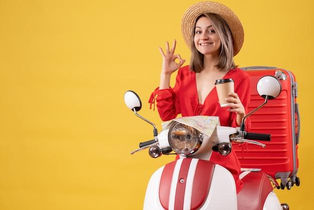 Vooraanzicht jonge dame in rode jurk met koffiekopje gebaren ok teken in de buurt van bromfiets