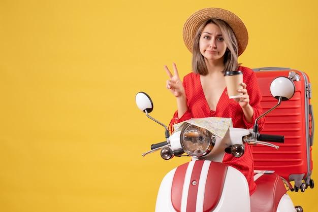 Vooraanzicht jonge dame in rode jurk met koffiekopje maken overwinningsteken in de buurt van bromfiets