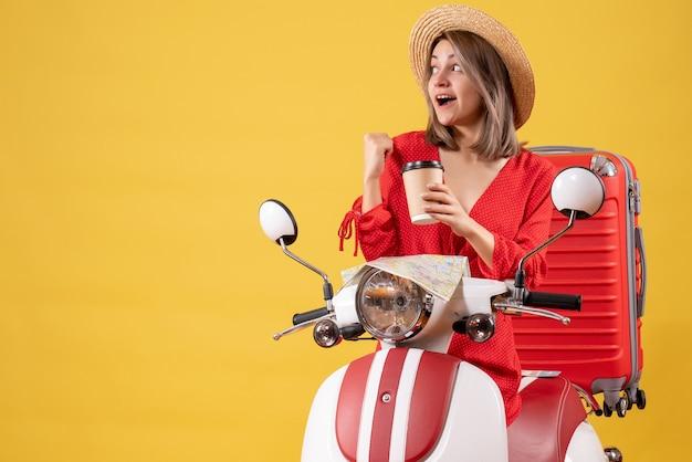 Vooraanzicht jonge dame in rode jurk met koffiekopje wijzend naar achter in de buurt van bromfiets