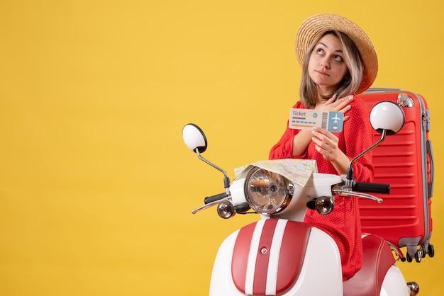 Vooraanzicht jonge dame in rode jurk met ticket omhoog kijkend op bromfiets