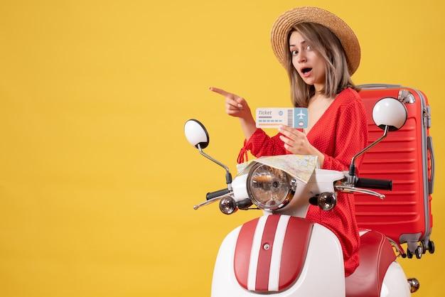 Vooraanzicht jonge dame in rode jurk met ticket wijzend naar links op bromfiets