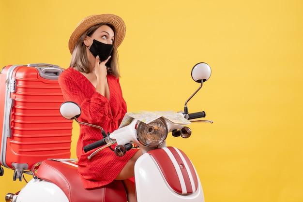 Vooraanzicht jonge dame in rode jurk op bromfiets die ergens aan denkt