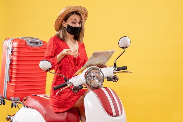 Vooraanzicht jonge dame in rode jurk op bromfiets kijken naar kaart