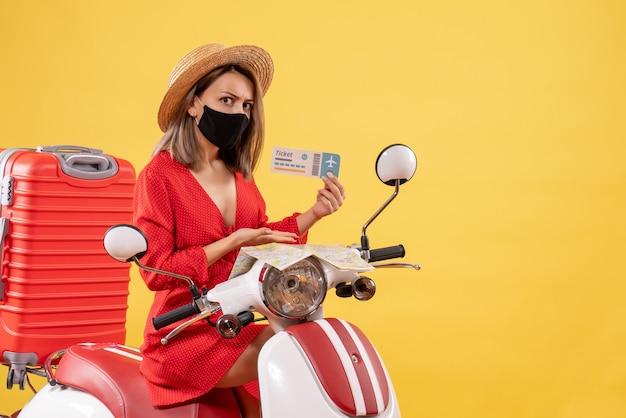 Vooraanzicht jonge dame in rode jurk op bromfiets met koffer met ticket