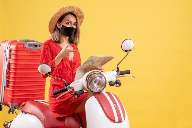 Vooraanzicht jonge dame in rode jurk op bromfiets wijzend op kaart in haar hand
