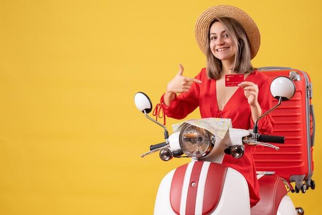 Vooraanzicht jonge dame in rode jurk wijzend op bankkaart op bromfiets