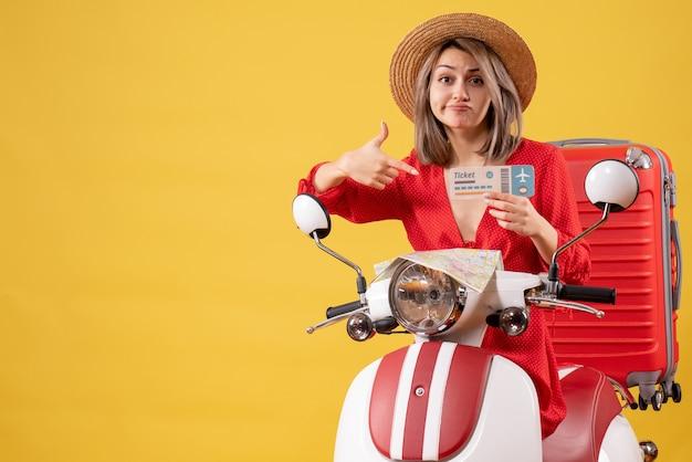 Vooraanzicht jonge dame in rode jurk wijzend op ticket op bromfiets