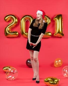 Vooraanzicht jonge dame in speciale pose ballonnen op rood