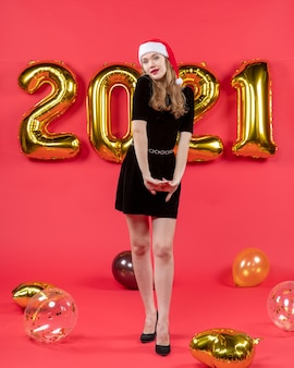 Vooraanzicht jonge dame in zwarte jurk ballonnen op rode nieuwjaarsfoto