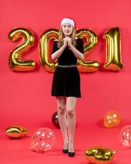Vooraanzicht jonge dame in zwarte jurk die ballonnen op rood wenst