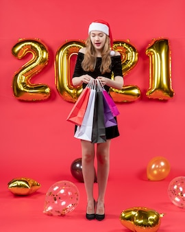 Vooraanzicht jonge dame in zwarte jurk die boodschappentassen bij elkaar houdt ballonnen op rood