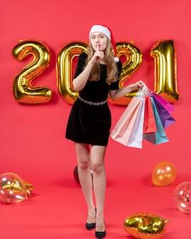 Vooraanzicht jonge dame in zwarte jurk die boodschappentassen vasthoudt en shh-tekenballonnen op rood maakt