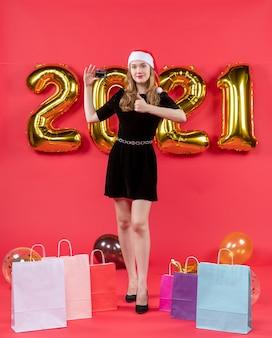 Vooraanzicht jonge dame in zwarte jurk die duim omhoog tekenzakken op vloerballons op rood maakt