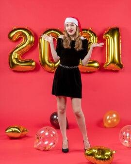 Vooraanzicht jonge dame in zwarte jurk die haar handen ballonnen op rood opent