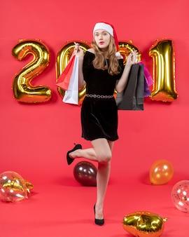 Vooraanzicht jonge dame in zwarte jurk die haar voet opheft met boodschappentassen ballonnen op rood