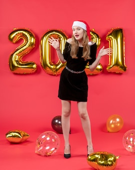Vooraanzicht jonge dame in zwarte jurk die handen ballonnen op rood opent