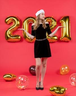 Vooraanzicht jonge dame in zwarte jurk die handen opent en naar juiste ballonnen op rood kijkt