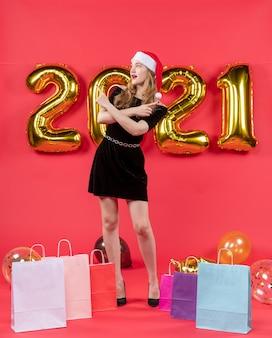Vooraanzicht jonge dame in zwarte jurk die handen tassen kruist op vloerballonnen op rood