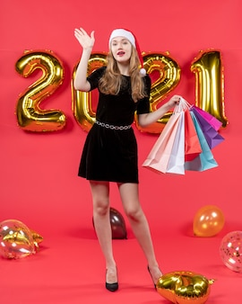 Vooraanzicht jonge dame in zwarte jurk die iemand begroet die boodschappentassenballonnen op rood vasthoudt