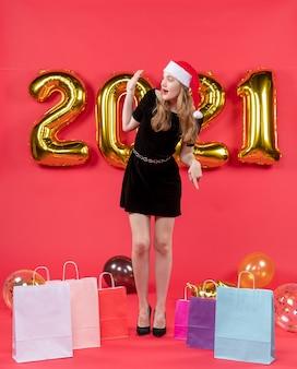 Vooraanzicht jonge dame in zwarte jurk die iemand tassen op vloerballons op rood begroet