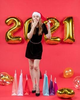 Vooraanzicht jonge dame in zwarte jurk hand op haar gezicht ballonnen op rood zetten