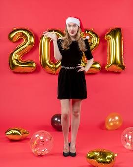 Vooraanzicht jonge dame in zwarte jurk hand op haar taille ballonnen op rood zetten