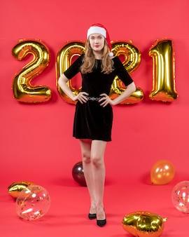 Vooraanzicht jonge dame in zwarte jurk handen op taille ballonnen op rood zetten
