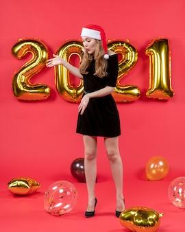Vooraanzicht jonge dame in zwarte jurk kijken naar ballonnen ballonnen op rood