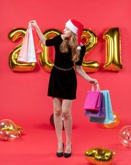 Vooraanzicht jonge dame in zwarte jurk kijken naar boodschappentassen ballonnen op rood