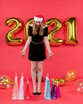 Vooraanzicht jonge dame in zwarte jurk kijken naar tassen op vloer ballonnen op rood on