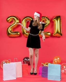 Vooraanzicht jonge dame in zwarte jurk kijkend naar linkerzakken op vloerballonnen op rood