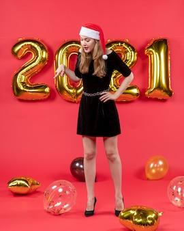 Vooraanzicht jonge dame in zwarte jurk kijkend naar vloerballonnen op rood