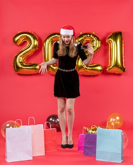 Vooraanzicht jonge dame in zwarte jurk kijkend naar vloerzakken op vloerballonnen op rood