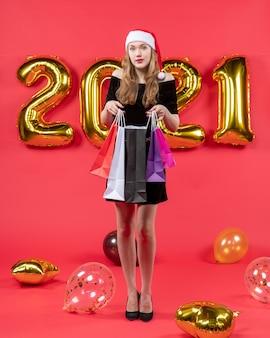 Vooraanzicht jonge dame in zwarte jurk met boodschappentassen ballonnen op rood
