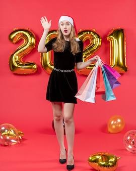 Vooraanzicht jonge dame in zwarte jurk met boodschappentassen die iemand ballonnen op rood begroet