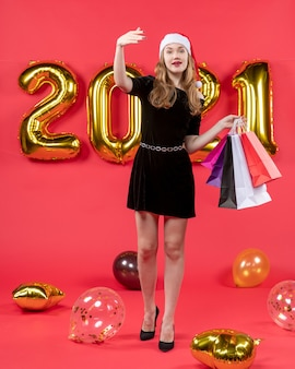 Vooraanzicht jonge dame in zwarte jurk met boodschappentassen die iemand ballonnen op rood roept