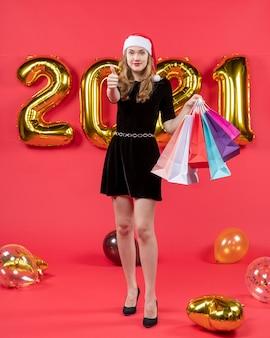 Vooraanzicht jonge dame in zwarte jurk met boodschappentassen en duim omhoog teken ballonnen op rood