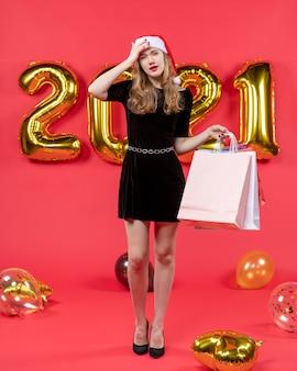 Vooraanzicht jonge dame in zwarte jurk met boodschappentassen en haar hoofdballonnen op rood
