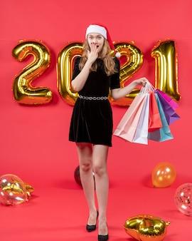 Vooraanzicht jonge dame in zwarte jurk met boodschappentassen en hand op haar gezicht ballonnen op rood
