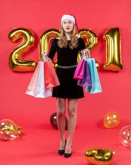Vooraanzicht jonge dame in zwarte jurk met boodschappentassen in beide handen ballonnen op rood