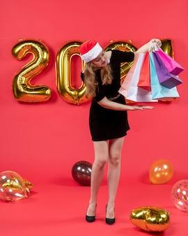 Vooraanzicht jonge dame in zwarte jurk met boodschappentassen in haar handen ballonnen op rood