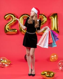 Vooraanzicht jonge dame in zwarte jurk met boodschappentassen kijkend naar juiste ballonnen op rood