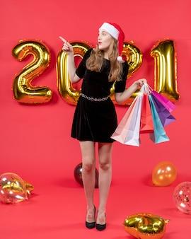 Vooraanzicht jonge dame in zwarte jurk met boodschappentassen wijzend op iets ballonnen op rood