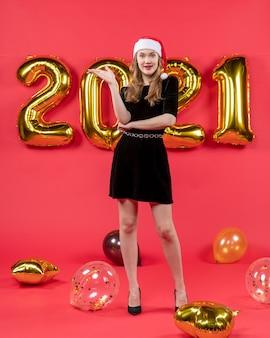 Vooraanzicht jonge dame in zwarte jurk met iets ballonnen op rood