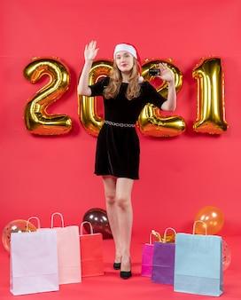 Vooraanzicht jonge dame in zwarte jurk met kaart die iemand aanroept op vloerballonnen op rood
