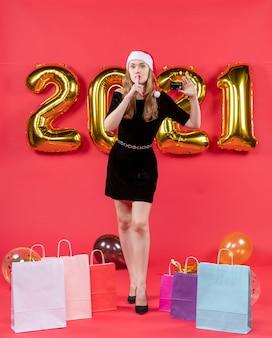 Vooraanzicht jonge dame in zwarte jurk met kaart die shh-tekenzakken maakt op vloerballonnen op rood