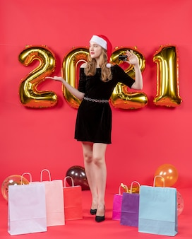 Vooraanzicht jonge dame in zwarte jurk met kaartzakken op vloerballonnen op rood